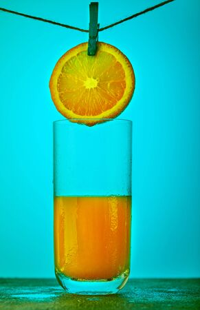 A slice of orange hanging on a rope with a clothespin and flowing orange juice into a glass on a blue background. Healthy eating concept.