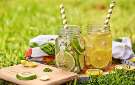 Refreshing drink with lemon and lime in special jars with straws on a wooden stand, shot in the morning on the green grass. Healthy eating concept.