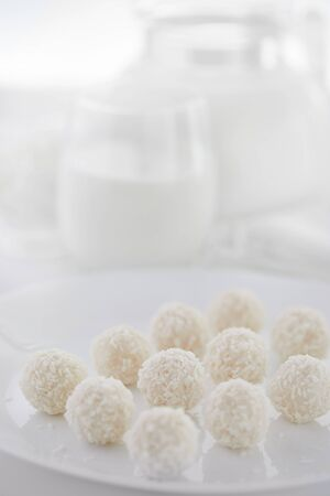 White chocolate candies with coconut filling with milk and cottage cheese in the background on a white background. High key photo.