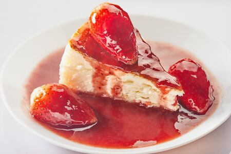 Cheesecake with strawberry jam on a white plate on a light background.