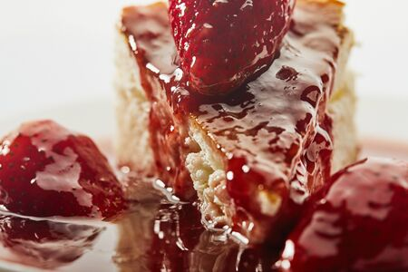 Cheesecake with strawberry jam on a white plate on a light background. Close up.