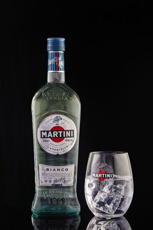Tel Aviv, Israel - January 8, 2020: Martini bottle and martini glass with ice isolated on a black background with reflection. Sajtókép