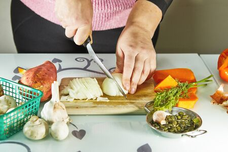 Woman slices onions on a wooden board in the kitchen. Female hands prepare cream soup with pumpkin and onions. Healthy eating concept.