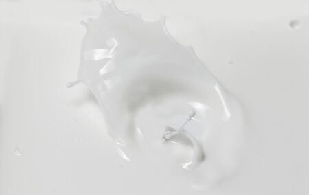 Fresh milk pouring making a crown splash in a milk pool. Top view, isolated on grey-white background.