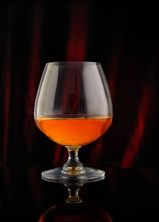 Glass with cognac on a red-black background with reflection. Reklamní fotografie