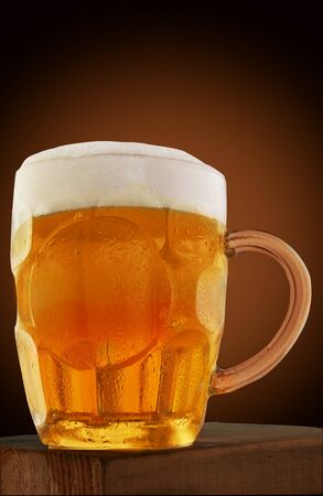 Beer in a mug with foam, on a wooden stand and a brown background.