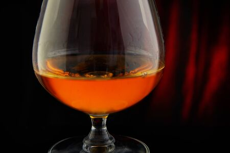 Glass with cognac on a red-black background with reflection. Close up.