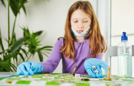 Life in quarantine coronavirus: games and activities for the child at home during quarantine covid-19. A cute girl in a mask and gloves plays a game with dice and chips. Selective focus.