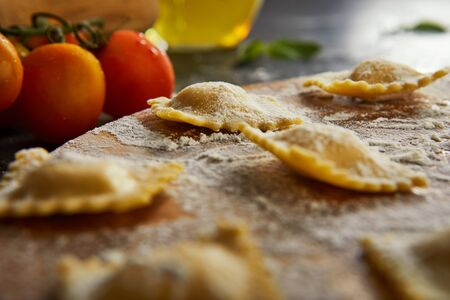 Tasty raw ravioli with flour, cherry tomatoes, sunflower oil and basil on a dark background. The process of making Italian ravioli. Side view.