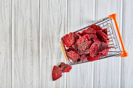 Diet healthy eating concept. Dried beet chips in a toy grocery cart on a white background. Organic natural food. Concept vegan shopping. Copy space.
