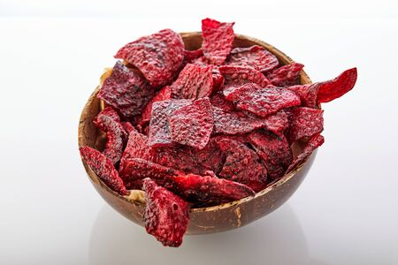 Diet healthy eating concept. Dried beet chips or baked beets in a bowl isolated on a white background. Organic natural food. Copy space. Zdjęcie Seryjne