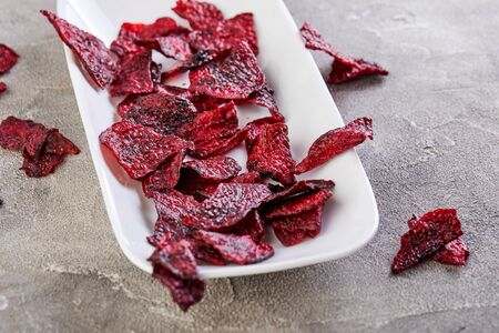 Diet healthy eating concept. Dried beet chips or baked beets in a white rectangular plate, on a gray concrete background. Organic natural food. Copy space.
