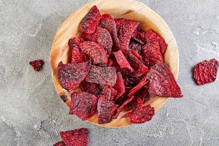 Diet healthy eating concept. Dried beet chips or baked beets in a wooden bowl, on a gray concrete background. Organic natural food. Copy space.