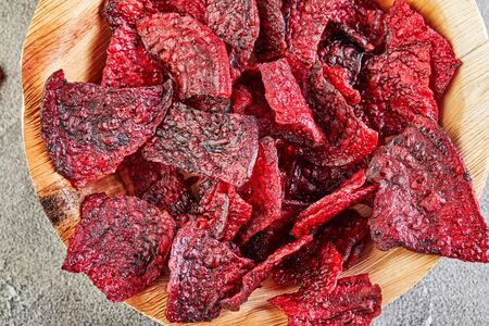 Diet healthy eating concept. Dried beet chips or baked beets in a wooden bowl, on a gray concrete background. Organic natural food. Zdjęcie Seryjne