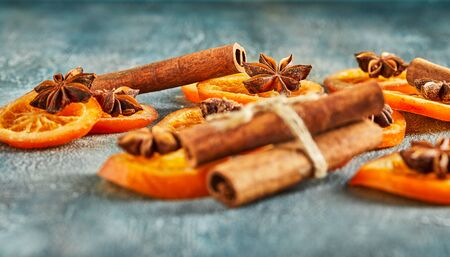 Slices of dried oranges or tangerines with anise and cinnamon, on a blue background. Vegetarianism and healthy eating. Copy space.