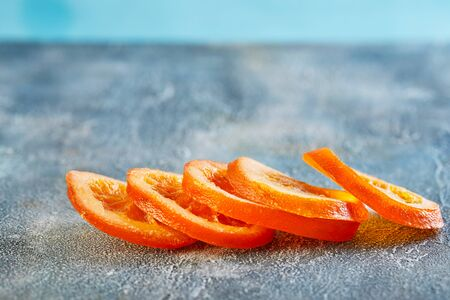 Slices of dried oranges or tangerines on a blue background. Vegetarianism and healthy eating. Copy space.