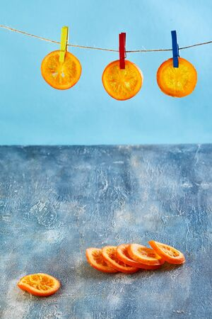 Slices of dried oranges or tangerines are hung on clothesline with clothespins on a blue background. Vegetarianism and healthy eating. Copy space.