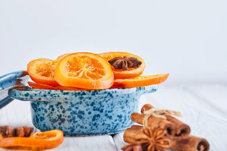 Slices of dried oranges or tangerines with anise and cinnamon in a blue bowl on a light background. Vegetarianism and healthy eating. Copy space.