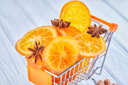 Slices of dried oranges or tangerines with anise and cinnamon in a supermarket cart on a light background. Vegetarianism and healthy eating. Copy space.