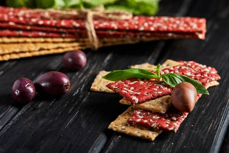 Beetroot and rye flour crackers with vegetables for making snacks on a black background. Vegetarianism and healthy eating.