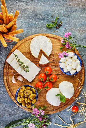 A variety of cheeses of different shapes and tastes with cherry tomatoes and smoked olives on a round wooden plate on a blue background. Flat lay. Copy space.