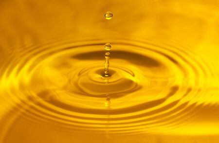 Yellow background, texture. Drops falling in water and circles walking on water, with reflection.