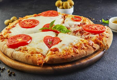 Italian pizza and ingredients for cooking on a black concrete background. Tomatoes, olives, basil and spices. Sliced triangle of pizza. Copy space for text. Side view