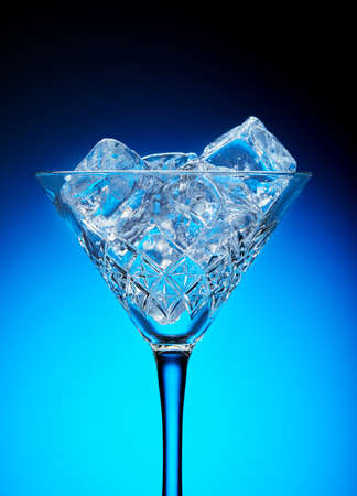 Ice in a martini glass on a blue background with a gradient.