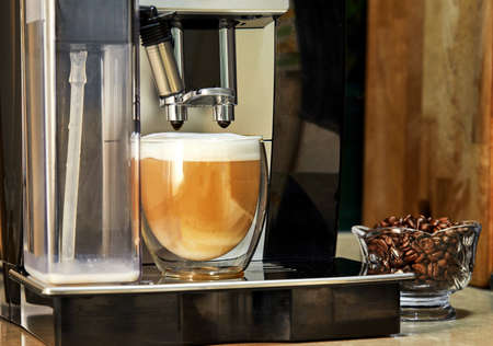Coffee machine makes cappuccino coffee in a transparent cup. Freshly brewed coffee concept.