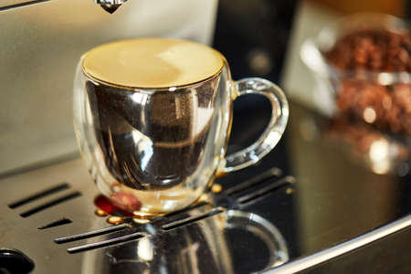 Espresso in a transparent cup, standing on a coffee machine with reflection. Freshly brewed coffee concept. 스톡 콘텐츠