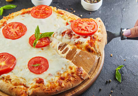 The delicious taste of pizza and slices of cheese with mozzarella and tomatoes. Triangle pizza with stretching cheese and spices. Stock fotó