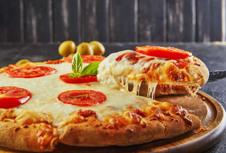 The delicious taste of pizza and slices of cheese with mozzarella and tomatoes. Triangle pizza with stretching cheese and spices. Copy space for text. Stock fotó