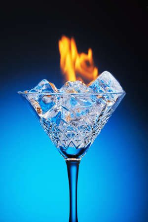 Ice in a martini glass and burning fire on a blue background with reflection and gradient. Stock fotó