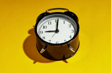 Black alarm clock with a hard shadow on a yellow background. Stock fotó