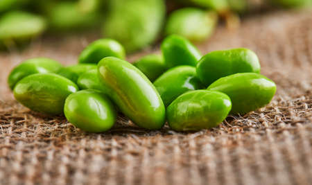 Edamame or soybeans are scattered on a brown sackcloth.