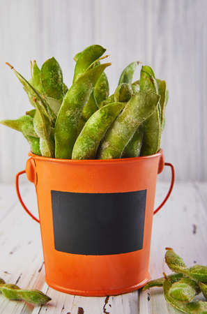 Frozen Edamame or soybeans in an orange bucket on a white wooden background. Place for Mock App.