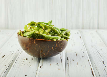 Frozen Edamame or soybeans in a wooden hemisphere on a white wooden background.