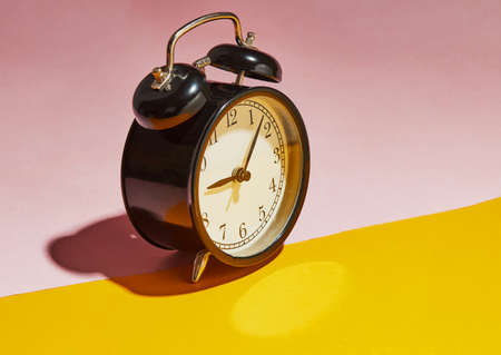 Black alarm clock with a hard shadow on a pink-yellow background. Stock fotó