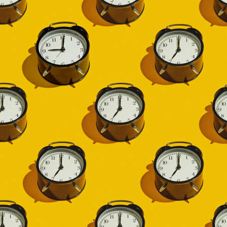 Pattern Black alarm clock with a hard shadow on a yellow background.