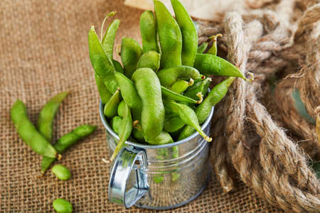 Edamame or soybeans in a shiny bucket on a brown sackcloth. Stock fotó