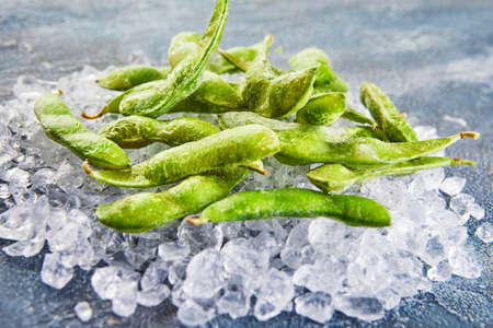 Frozen Edamame or soybeans in the mix with crushed ice on a blue background. Stock fotó