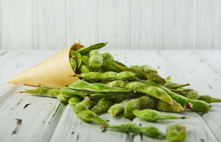 Frozen Edamame or soybeans poured from a cone on a white wooden background.