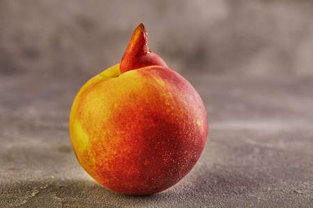 Ugly fruit or vegetable. Severely malformed mutant peach on grey background. Ugly fruit is not in high demand. Stock fotó