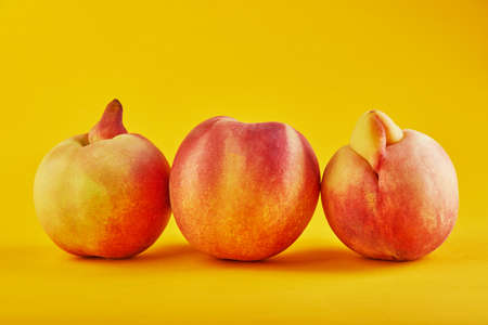 An ugly fruit or vegetable. Fresh peach and two Very ugly peach mutants on an orange background. Ugly fruits are not in high demand.