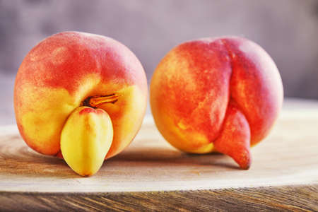 An ugly fruit or vegetable. A very ugly peach mutant on a wooden stand. Ugly fruits are not in high demand.
