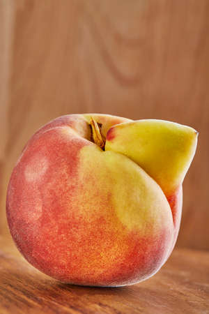 ugly fruit or vegetable. Heavily ugly peach mutant on a wooden background. Ugly fruits are not in high demand.