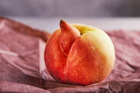 Ugly fruit or vegetable. A highly ugly peach mutant on purple paper. Ugly fruits are not in high demand. Stock fotó