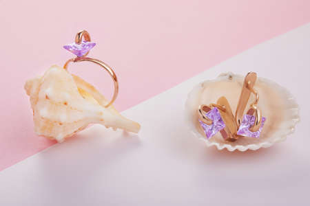 Gold earrings and amethyst ring in sea shells on a white-pink background.