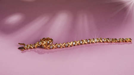 Golden bracelet with diamonds on a pink background with the shadow of a monstera.