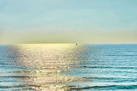 View of the Mediterranean Sea with a sailboat from the hill at sunset. Stock fotó